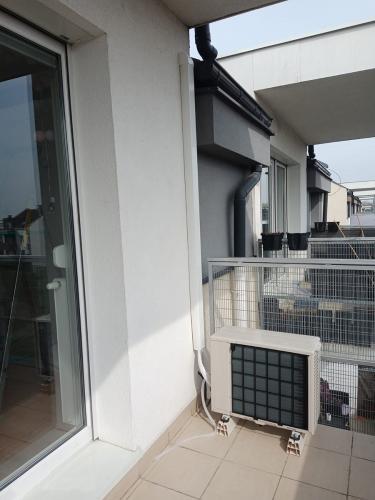 Klimatyzator agregat Fuji Electric RSG12KMCC na balkonie rurami do ściany